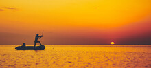 Silhouette Of A Fisherman Fishing In Sunset Time On The Open Sea.