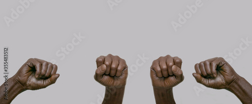 Tablou Canvas Black African-American human hands with raised fists in the air on a gray isolated background