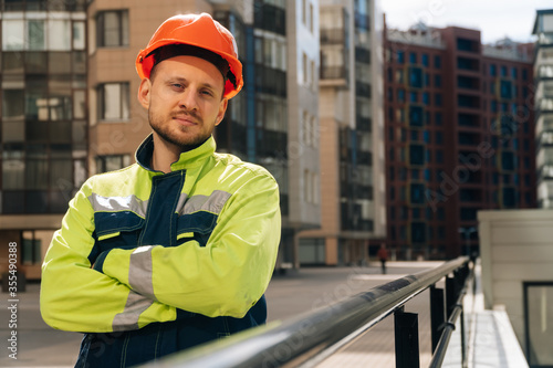 Foto young handsome smiling architect supervising a construction holding blueprints