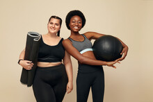 Workout. Diversity Women Portrait. Multi-Ethnic Slim And Plus Size Models Against Beige Background. African And Caucasian Women In Black Sportswear Holding Pilates Ball And Mat. Fitness As Lifestyle.