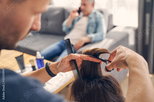 Fotografía Concentrated man cutting hair with scissors and comb