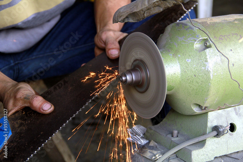 Blacksmith's hands sharpening a carpenter's saw using a bench grinder Canvas Print