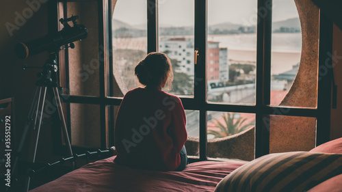 Girl looking through the window of her room sitting on the bed Slika na platnu