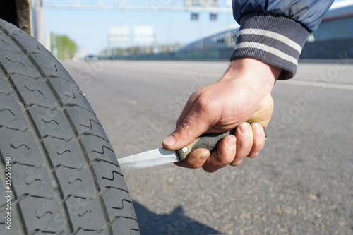 A man holds a knife in his hand and cuts a car tire with it. Canvas Print