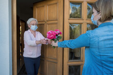 Senior Woman With Face Mask Gets Flowers At The House Door From Neighbor Woman