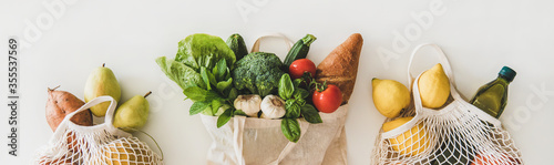 Obraz Online grocery healthy shopping. Flat-lay of fruit, vegetables, greens, bread and oil in eco-friendly bag over white background, top view, wide composition. Shop online during pandemic of coronavirus - fototapety do salonu
