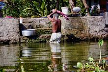 A Man Washing His Cloths In An...