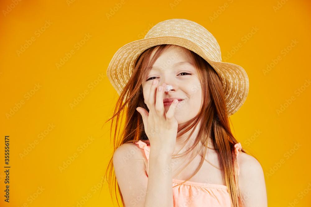 Fototapeta jolie jeune enfant fille caucasienne aux cheveux longs châtains mettant de la crème solaire sur son visage pour protéger sa peau sur fond jaune de studio