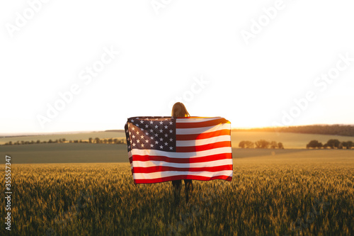 Carta da parati Beautiful girl with the American flag in a wheat field at sunset