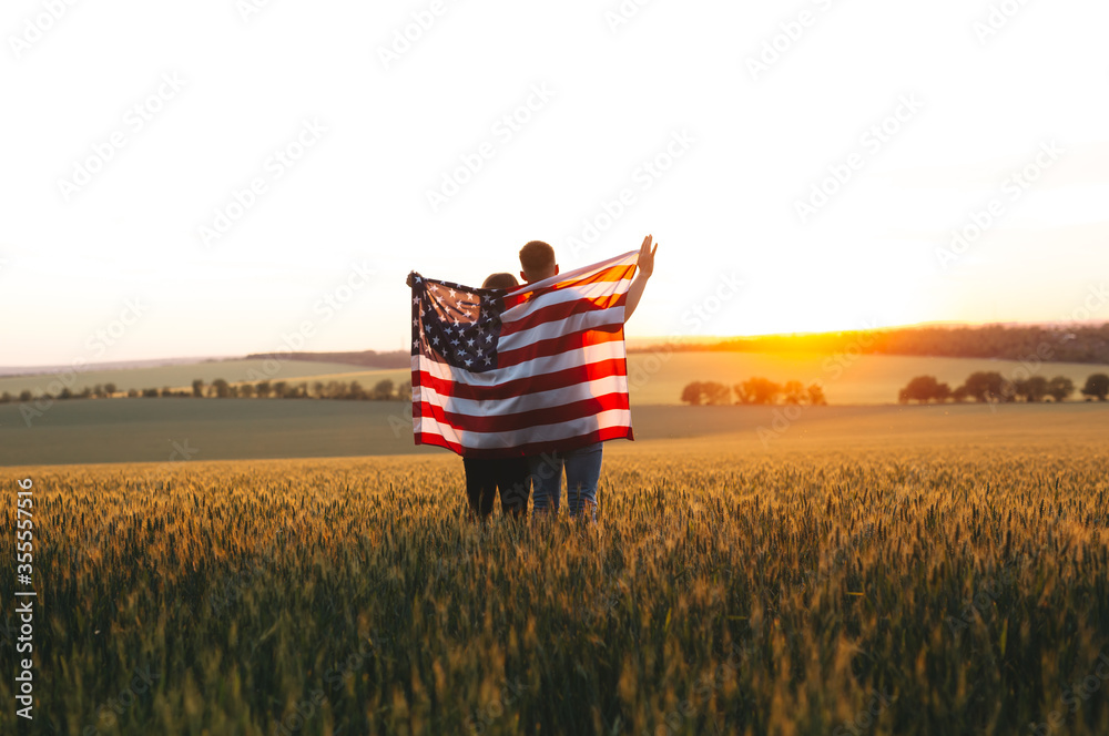 Fototapeta Image of  young couple with the American flag in a wheat field at sunset.  Independence Day, 4th of July.