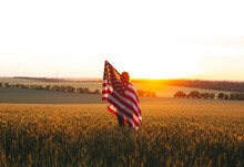 Beautiful Girl With The American Flag In A Wheat Field At Sunset. 4th Of July.  Independence Day.
