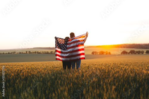 Fototapeta Image of  young couple with the American flag in a wheat field at sunset.  Independence Day, 4th of July. obraz