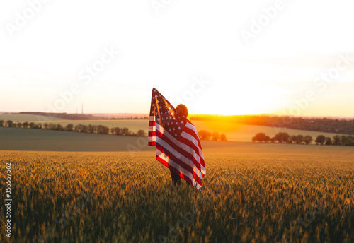 Fototapeta Beautiful girl with the American flag in a wheat field at sunset. 4th of July.  Independence Day. obraz