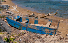 Old Wooden Rowboat Sits Abandoned Among Driftwood, Boulders, Seaweed And Shells On The Beach With Blue Water In The Boackground.