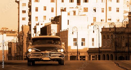 A classic car driving in a street in Havana Canvas Print