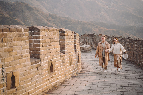 Fototapeta young couple running and twirling at the Great Wall of China. Newly married couple on their honeymoon to the Great Wall of China near Beijing China. obraz