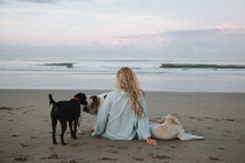 A Woman And Dogs Look At The Ocean. Freedom, Harmony
