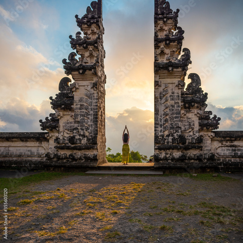 Foto One unrecognisable woman praying at the entrance of a temple, Bali, Indonesia