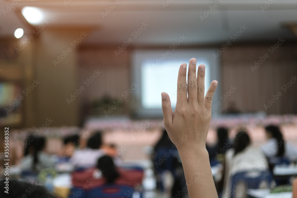 Fototapeta Audience or students raising hands up at conference to answer question while speaker speech at seminar hall with crowd groups, arms of large group in classroom for vote or questions