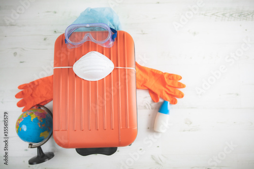 Cuadros en Lienzo Travel bag suitcase with earth globe, gloves, mask and head protection from viruses and flu influenza