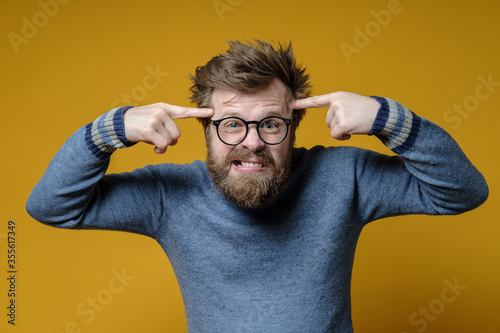 Angry shaggy man with glasses and an old sweater holds index fingers on his temples, proving to interlocutor that he is an idiot Wallpaper Mural