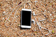 mobile phone with earphone in the sand on the beach