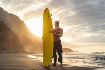 Happy fit senior having fun surfing at sunset time - Sporty bearded man training with surfboard on the beach - Active elderly people lifestyle and extreme sport concept