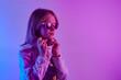 Leinwandbild Motiv Teen girl in sunglasses standing and posing over trendy blue neon light. Portrait of millennial pretty teenager.