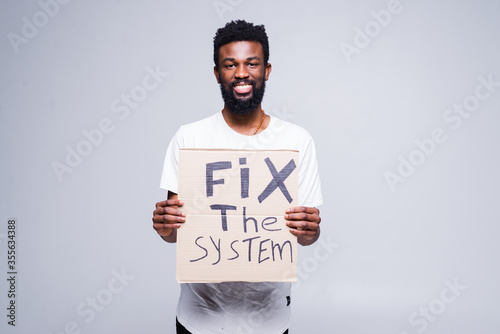 Canvas-taulu Young african man holding a cardboard poster with the message text Fix the system isolated on white background, Concept on the theme of protest for police brutality and racism