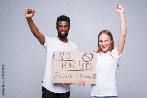 Obraz na plátne Young african man and coucasian woman holding a cardboard poster with the message text END RACISM isolated on white background, Concept on the theme of protest for police brutality and racism