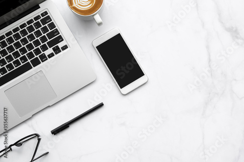 Obraz White marble office desk table with laptop computer, smartphone with blank screen, cup of latte coffee and office supplies. Top view with copy space, flat lay. - fototapety do salonu