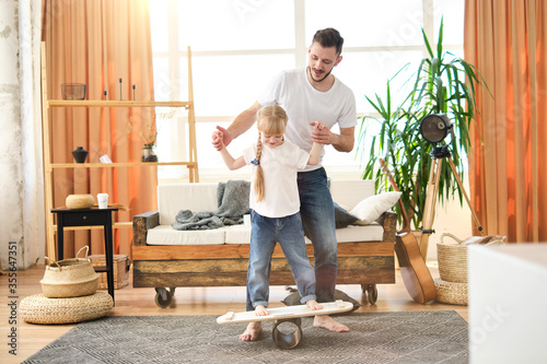 Father and daughter. Handsome young man teach little cute girl to keep balance on board at home, have fun. Dad and child laugh. Father's day.