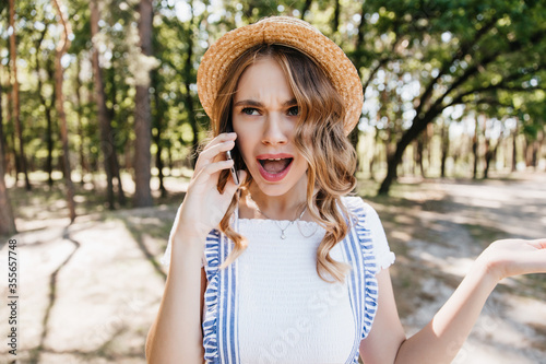 Photo Shocked fair-haired girl standing in park and talking on phone