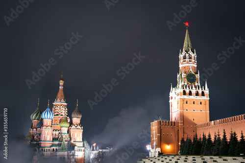 St. Basil's Cathedral and Spasskaya tower on Red Square in Moscow in the night haze with the fog. Red Square In Night. Moscow, Russia © Maksim