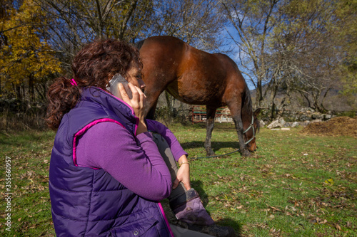 Fototapeta Girl chatting on a smart phone with bay horse behind grazing. obraz