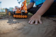 Little Kid Playing Excavator Toy On The Sand Ground