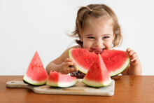 Smiling Toddler Girl Eating Watermelon At Kitchen Table