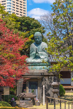 Bronze Statue Of Buddha Shaka Nyorai With A Stone Lantern And The Sentence May Peace Prevail On Earth On A Peace Pole Project's Pole In The Tennoji Temple Of Yanaka.