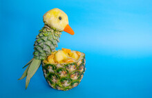 Sliced ​​fruits In Pineapple Bowl Decorated With Parrot Carved From A Pineapple On Blue Light Background With Copy Space. Food Art, Food Humor And Carving. Pineapple's Parrot Bird