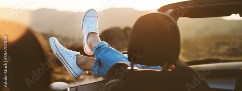 Obraz A young girl rests and pushes her shoes out of the convertible to enjoy the view - fototapety do salonu