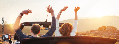 Obraz A loving couple enjoying the sunset and having fun in a convertible - fototapety do salonu