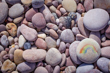 Pebbles On The Beach And Rainbow