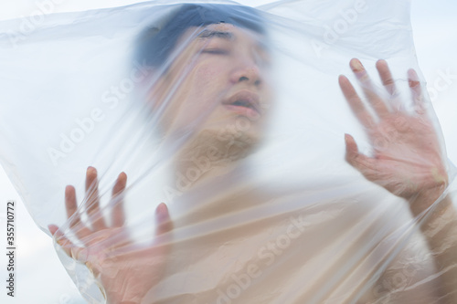 Asian gay man is wearing a plastic bag on his head that has suffocated a concept to stop using plastic and environmental pollution or stops marine and world pollution Wallpaper Mural
