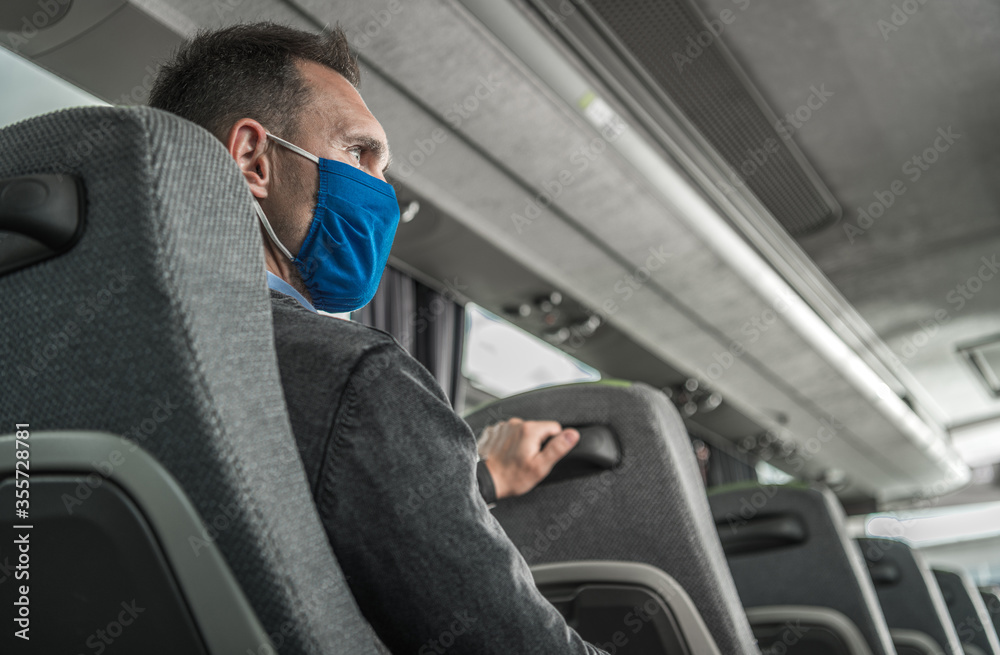 Fototapeta Men in Safety Breathing Mask on His Face Traveling Alone in a Bus Coach