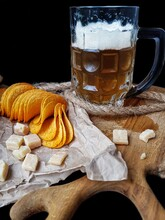 A Glass Of Beer With Foam On A Dark Background With A Snack Of Chips And Cheese On Craft Paper And A Wooden Kitchen Board.