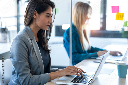 Two business women work with laptops on the partitioned desk in the coworking space. Concept of social distancing.