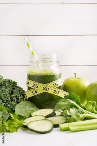 Health concept. Healthy green smoothie and tape measure and ingredients on white - superfoods, detox, diet, health, vegetarian food concept surrounded by ingredients