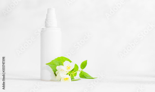 Fototapeta Unbranded skincare products plastic bottle with dispenser and flacons. Tube for cream shampoo. Green jasmine flowers and their shadows on the white background isolated. Mockup and copy space obraz na płótnie