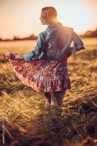 Photo Tätowierte junge Frau beim Sonnenuntergang im Weizenfeld