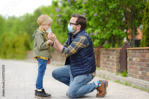 Man wearing facemask putting face mask on child on street of city or public park Canvas-taulu